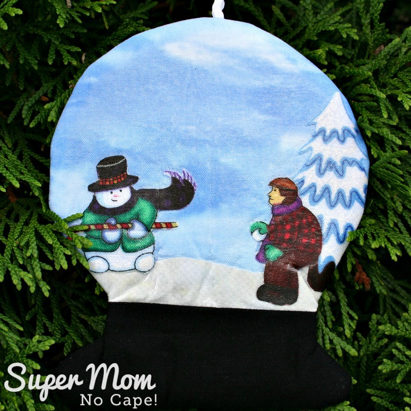 Snowman with green coat and cane snow globe