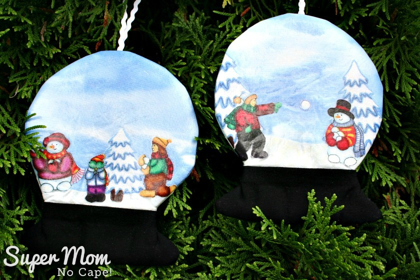 Two more snowglobes with snowmen and children having snowball fight