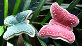 Two Beaded Felt Butterflies on a palm leaf branch