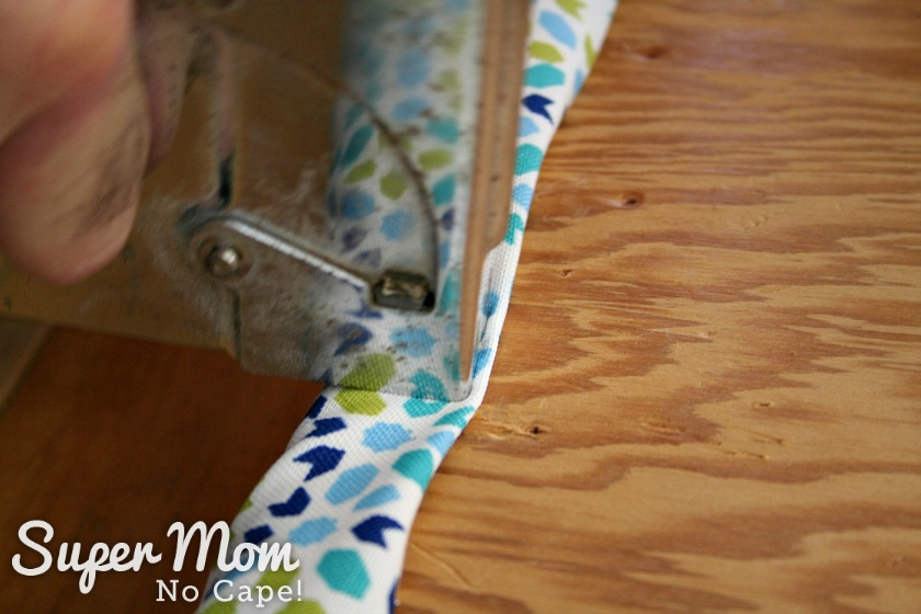 Stapling the upholstery fabric to the bottom of the seat cushion