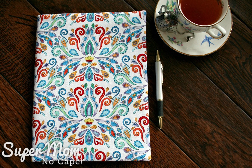 Angel fabric journal sitting beside a cup of tea and a pen