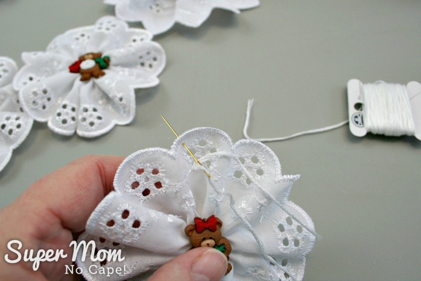 Adding an 8 inch length of white embroidery floss to make a hanger for the Christmas Button Lace Ornament
