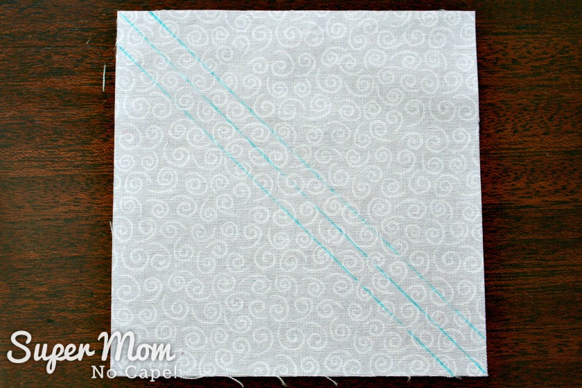 Diagonal lines drawn on white square of fabric