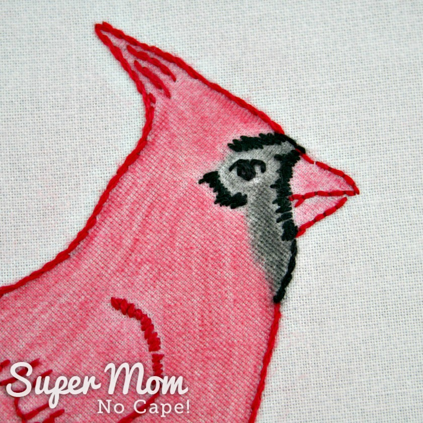 Head of the embroidered cardinal with crayon coloring