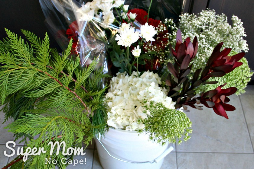 Lots of flowers in a white bucket to make a DIY Christmas Floral Arrangement