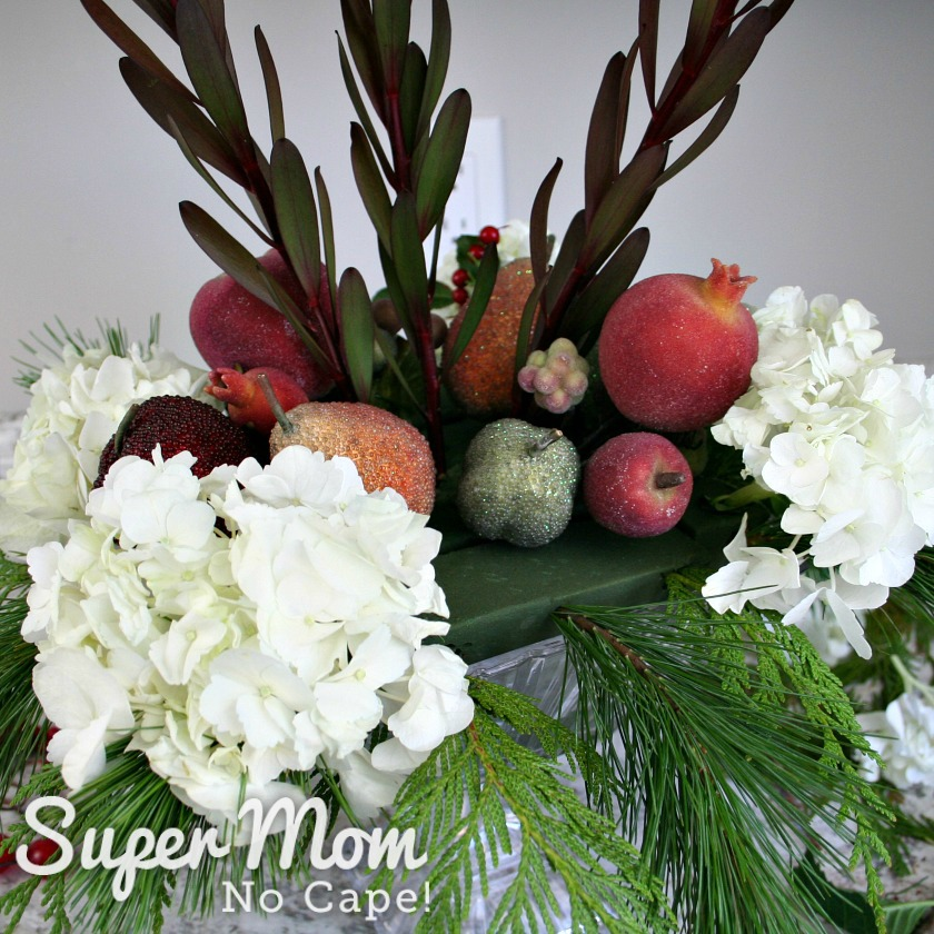 More faux sugared fruit added to the DIY Christmas floral arrangement