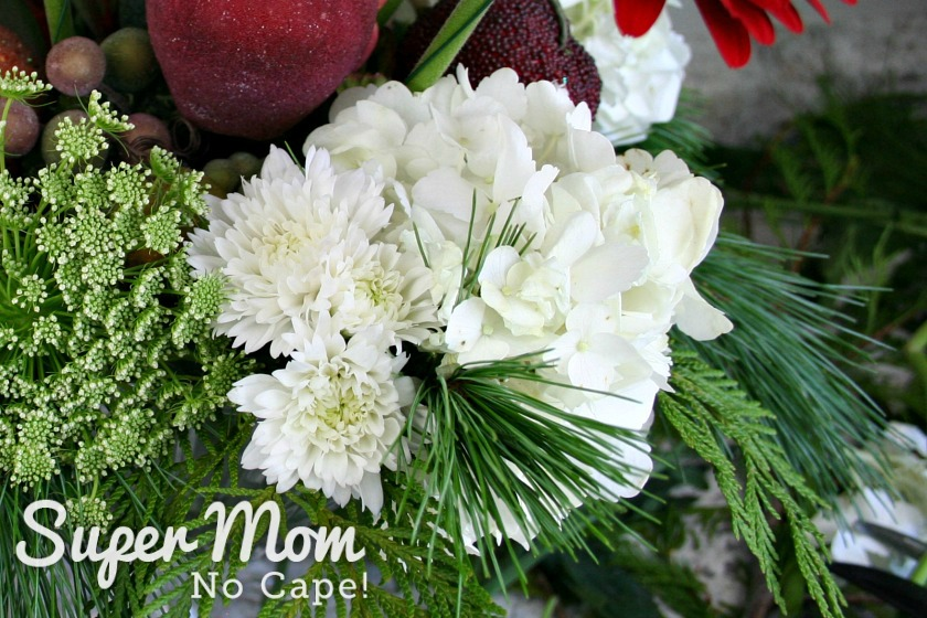 Filling in the Christmas floral arrangement with white winter mums