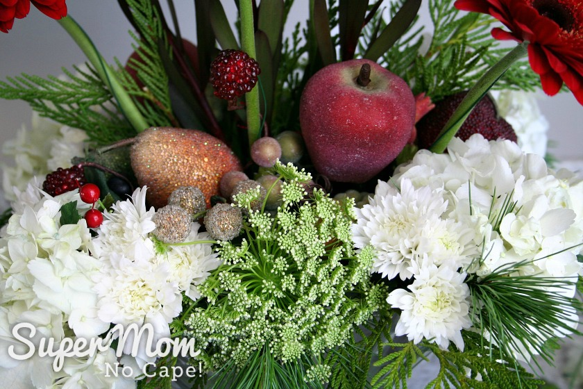 Addition faux sugared fruit and winter greenery added to the DIY Christmas floral arrangement