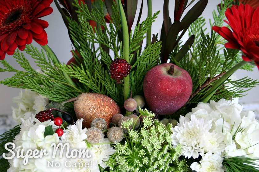 Several cedar leafs added to the DIY Christmas floral arrangement