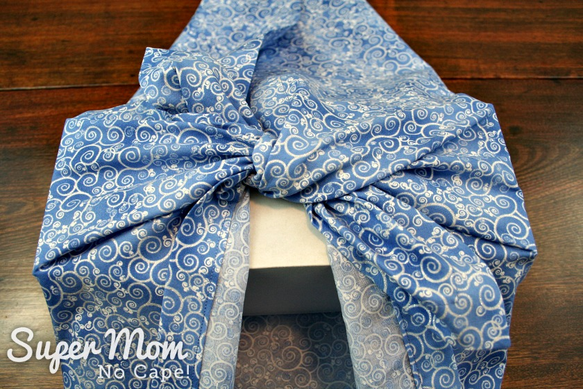 Tying first knot in blue Christmas furoshiki