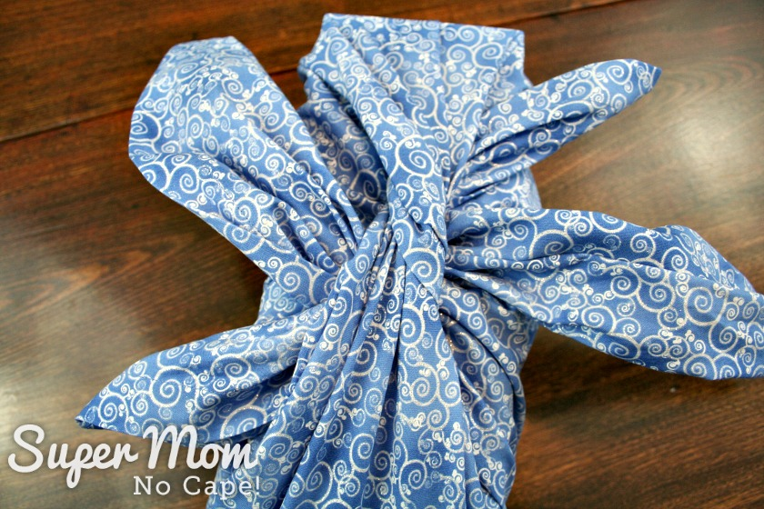 Getting the ends in position to tie the second knot on the blue Christmas furoshiki