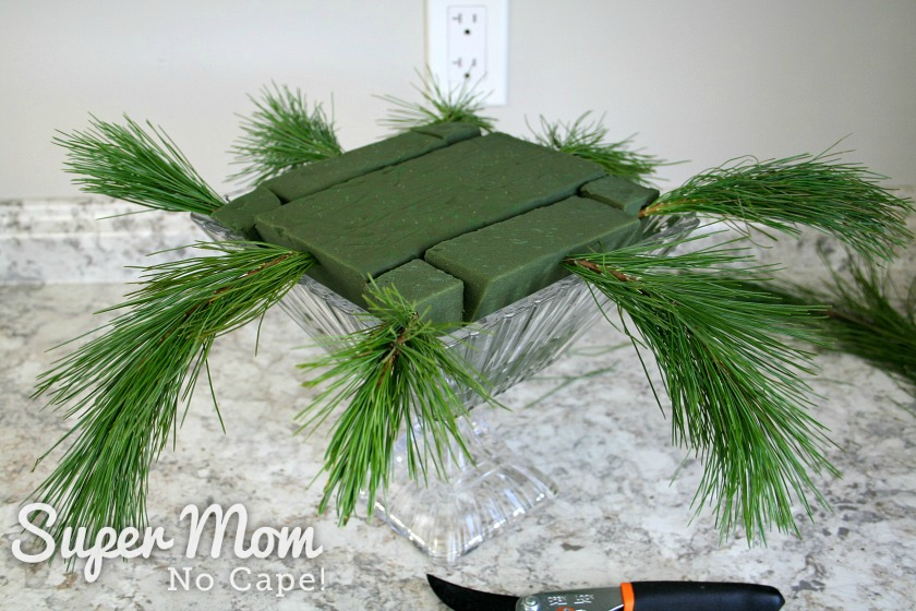 Adding the first layer of winter greenery to the DIY Christmas flower arrangement