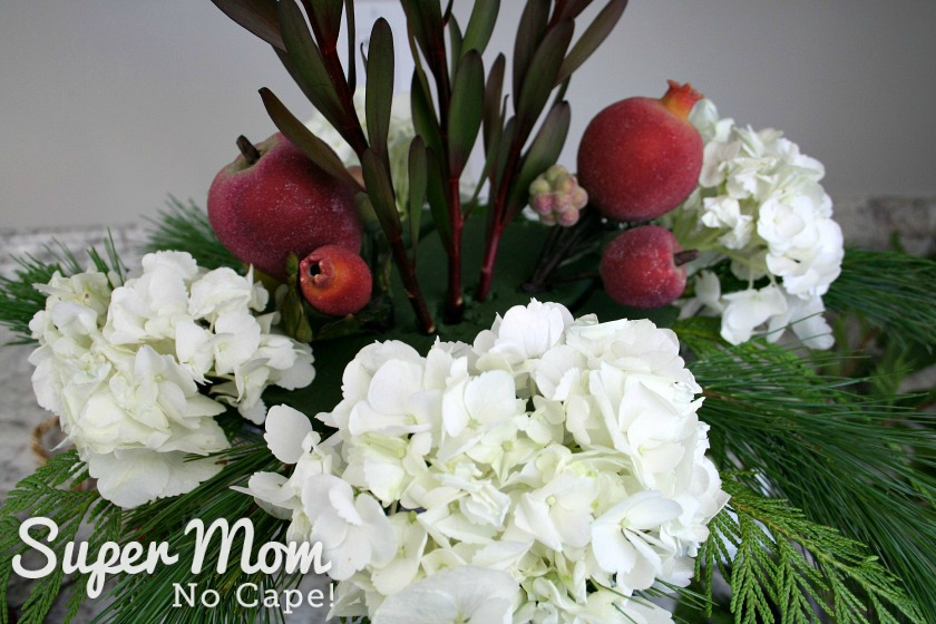 Hydrangeas and faux sugared fruit added to the DIY Christmas floral arrangement