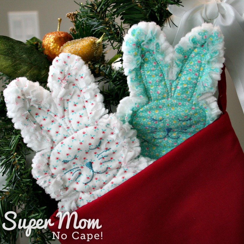 A white rag quilt bunny and a blue rag quilt bunny in the top of a stocking
