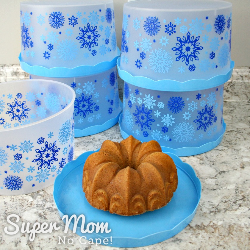 Bundt cake on lid of cake container with 4 containers in the background