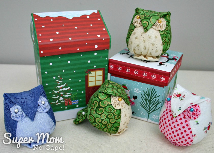 Four Archimedes Owl Pincushions sitting on and in front of small gift boxes
