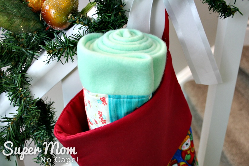 Pale green patchwork fleece scarf rolled up in the top of a stocking