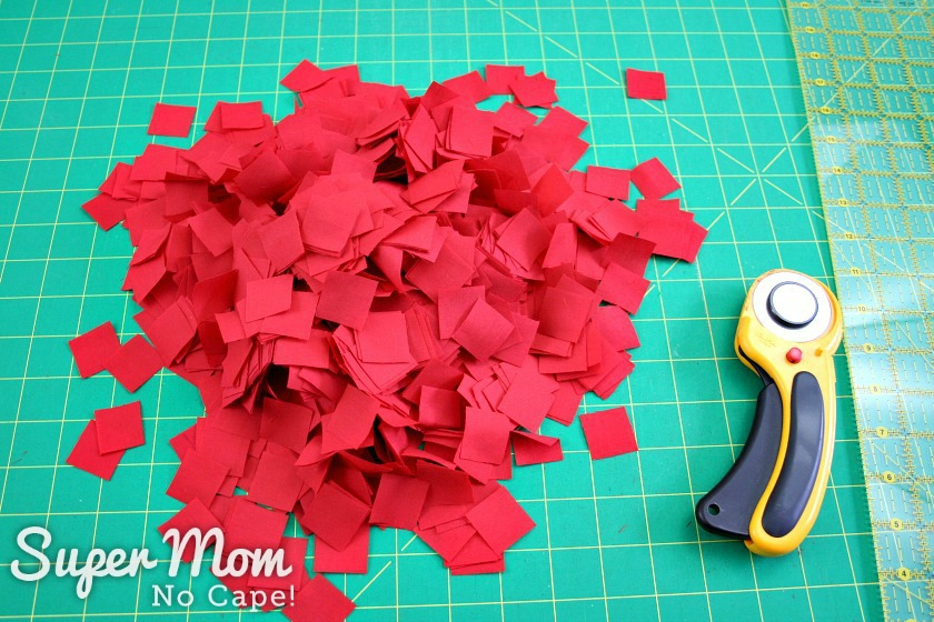 Pile of one inch squares of red fabric cut and ready to make the Poke and Push Fabric Christmas tree