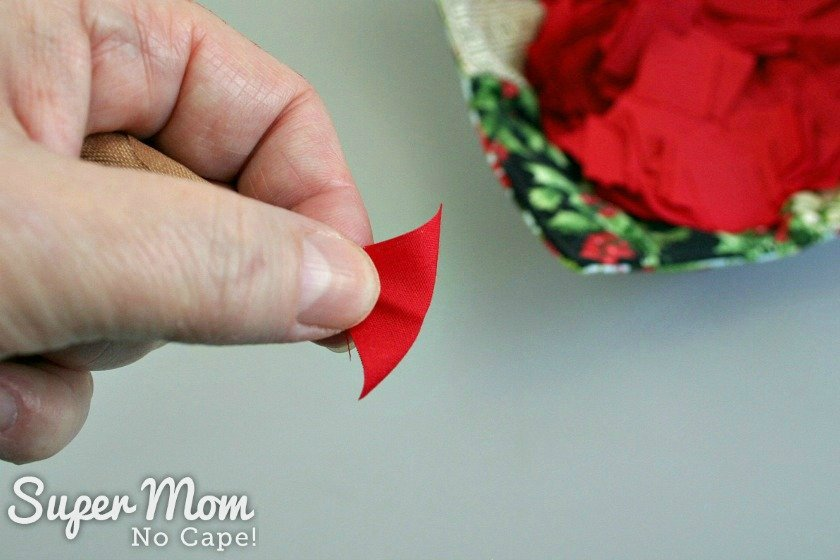 Poking the toothpick into the red fabric square for the Poke and Push Fabric Christmas Tree