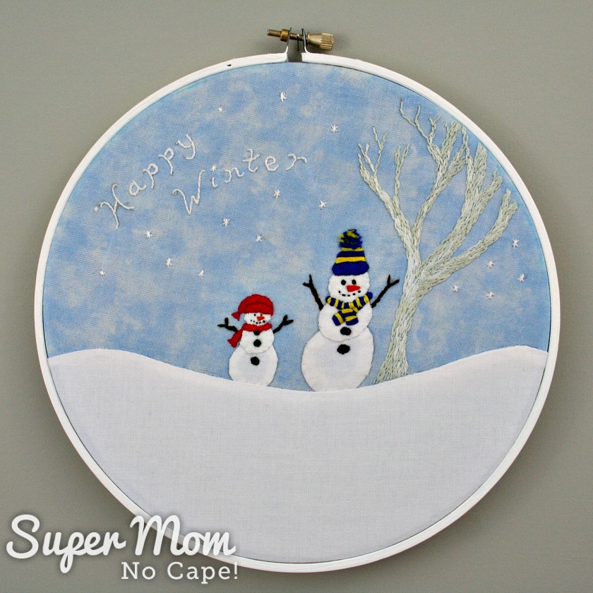 Happy Winter Snowmen Embroidery framed in a white embroidery hoop