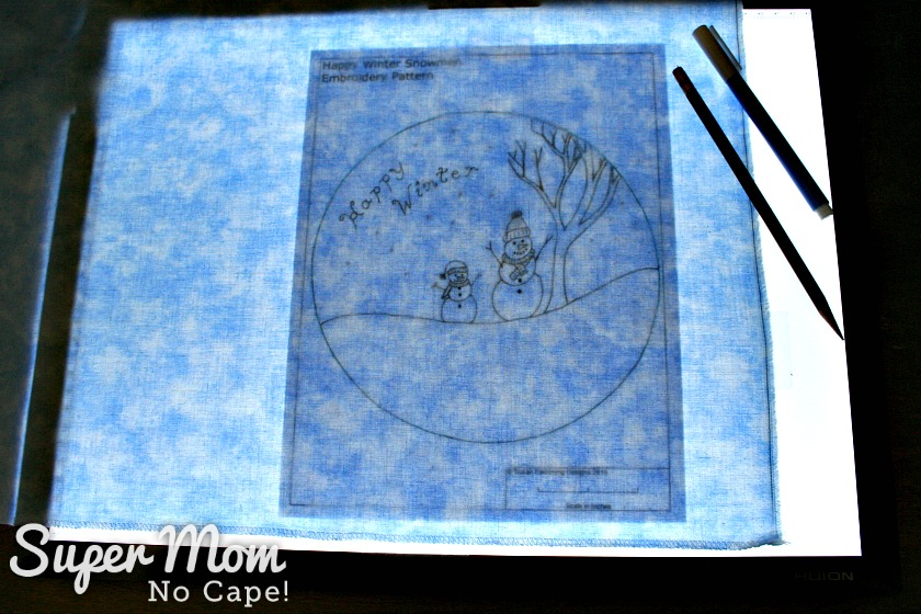 The Happy Snowmen Embroidery Pattern being traced onto blue fabric using a Huion lightbox