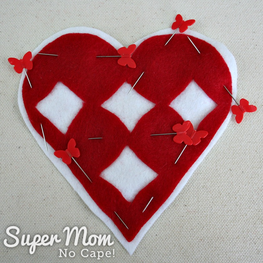 Cutwork red felt heart centered and pinned on white felt heart to make the I Heart Diamonds and Roses Sachet
