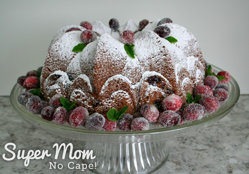 Cranberry Coffee Cake decorated with sugared cranberries and mint leaves on glass cake stand
