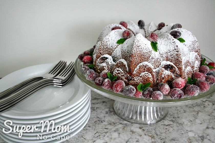 Cake stand with Cranberry Coffee Cake sitting beside a stack of plates and forks