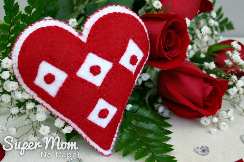 Close up photo of the I Heart Diamonds and Roses sachet with a bouquet of red roses in the background