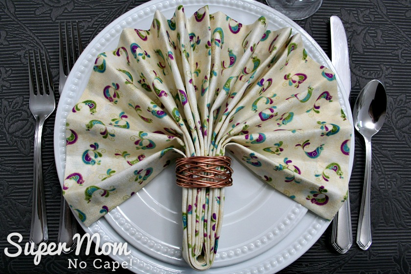 Fan folded napkin with brass napkin ring on white plates