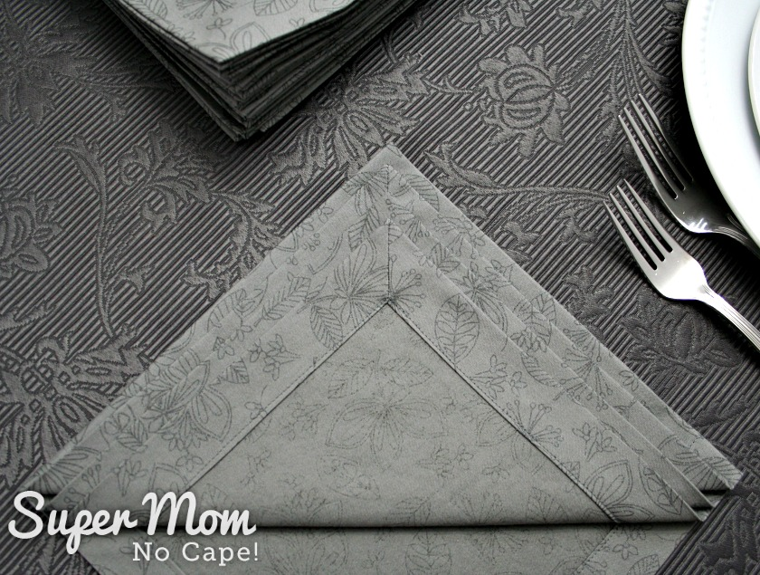 Folding one of the grey print napkins with mitered corners