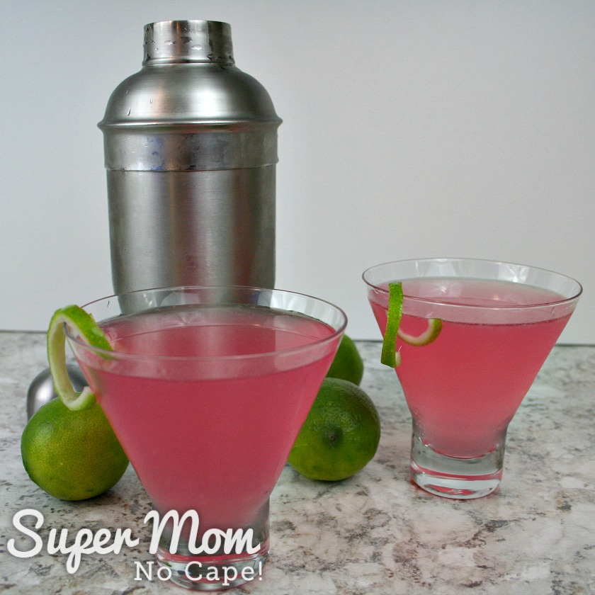 Two glasses of Cosmopolitan Cocktail with curls of lime rind and a cocktail shaker and limes in the background