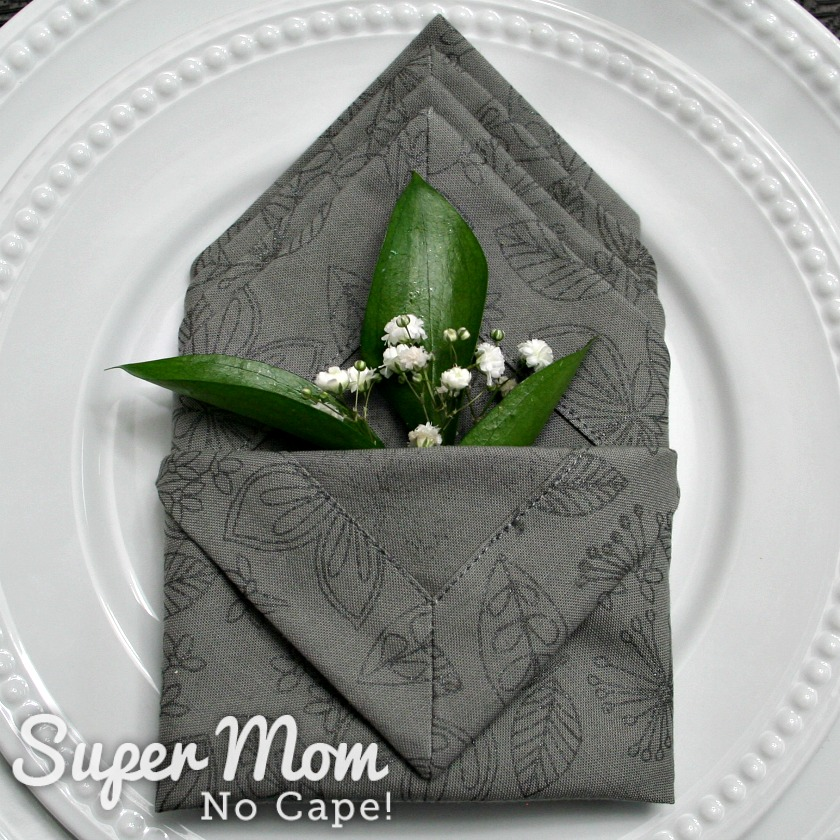 Greenery and babys breath in pocket of folded napkin