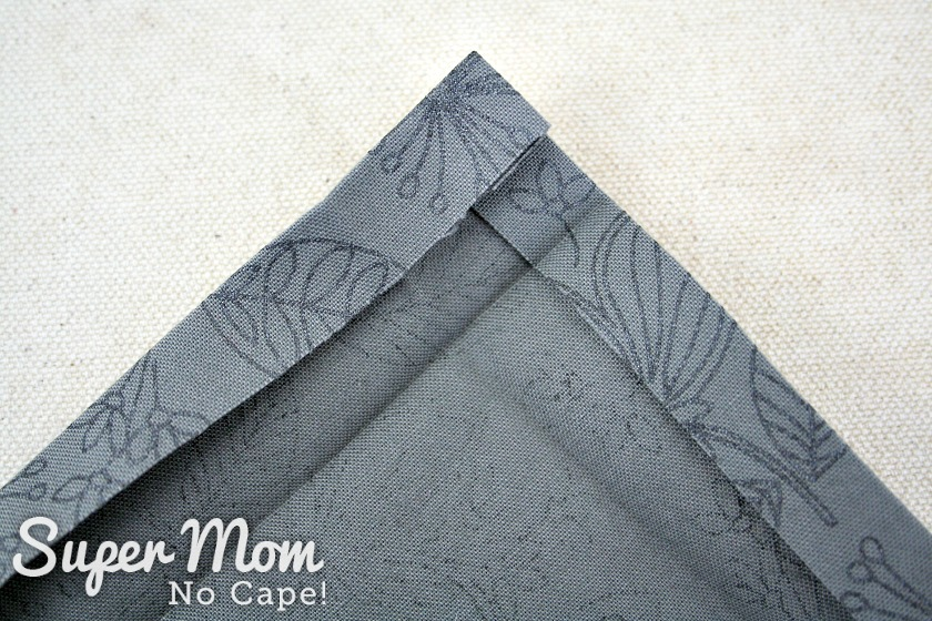 One inch pressed seam opened to reveal creases to make the mitered corners on the napkin.