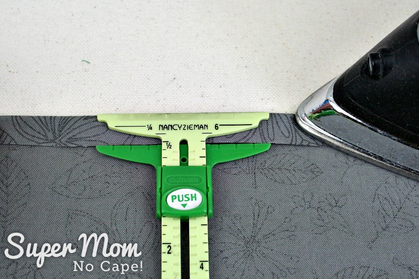 Nancy Zieman sliding ruler being used to use measure half inch fold under on napkin