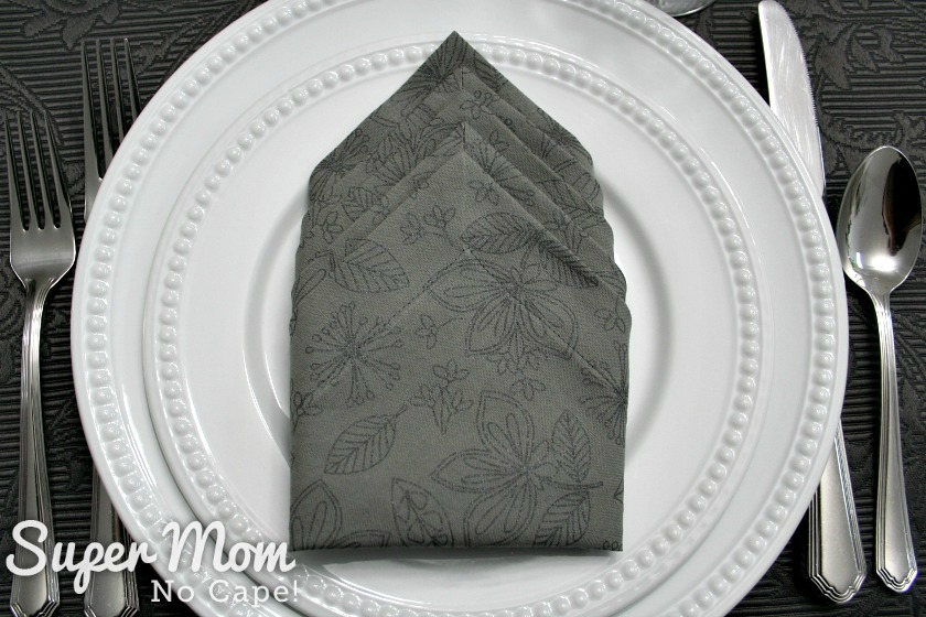 Place setting with grey print napkin with mitered corners in the center of white plates