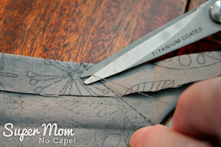 Scissors trimming off the thread tails close to fabric on the mitered corner