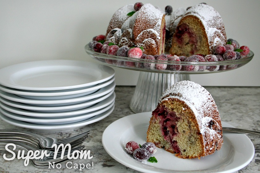 A serving of Cranberry Coffee Cake on a white plate with the rest of the cake on a cake stand in the background