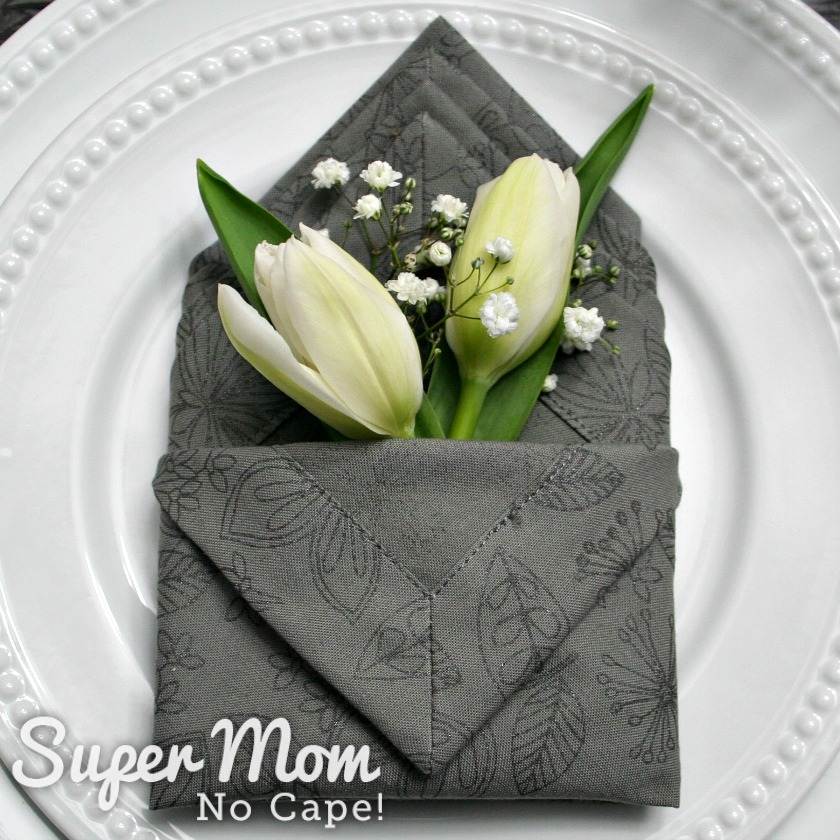 Two white tulips and some baby's breath in the grey napkin pocket
