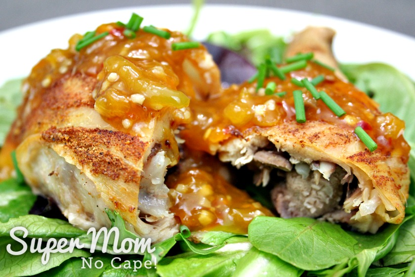 Baked chicken leg cut in half topped and placed on a bed of salad greens topped with Homemade Orange Sauce
