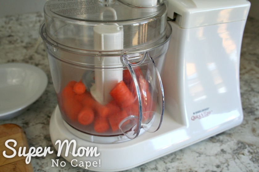 Coursely chopped carrots in the bowl of a food processor