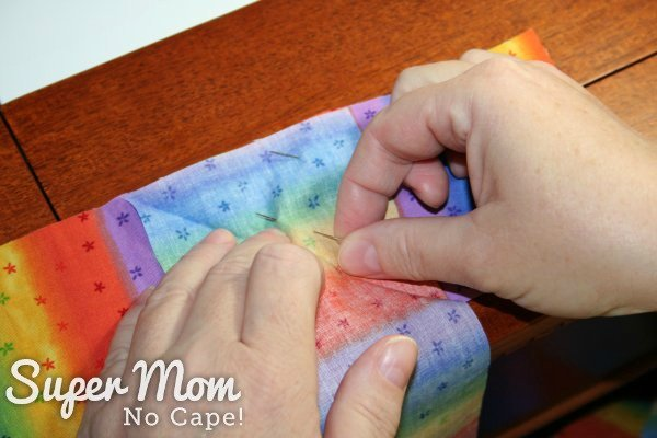 Adding the second pin to secure the two strips of striped fabric together