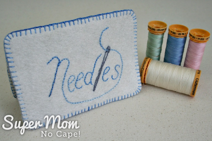 Needle Book case with Needles embroidered on it standing beside 4 spools of thread