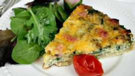 A single serving of crustless quiche with mixed green salad and tomato rose garnish on a white plate