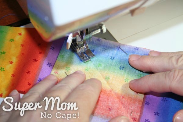 Sewing along the pressed crease in the top strip of striped fabric