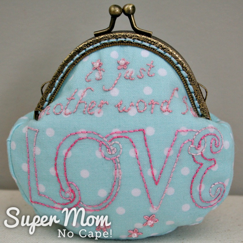 Back of the embroidered coin purse with the words is just another word for Love embroidery