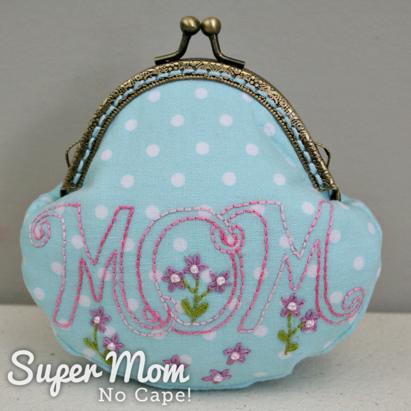 Front of the blue with white polka dot coin purse with MOM embroidered on it
