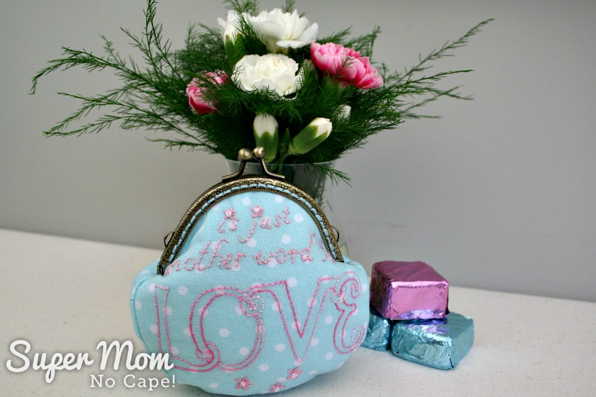The words is just another word for Love embroidered on a blue polka dot coin purse with vase of flowers and chocolates in the background