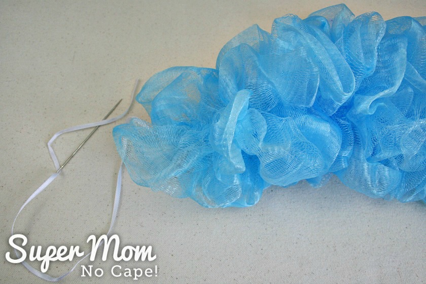 Blue mesh of unraveled shower puff gathered onto white ribbon