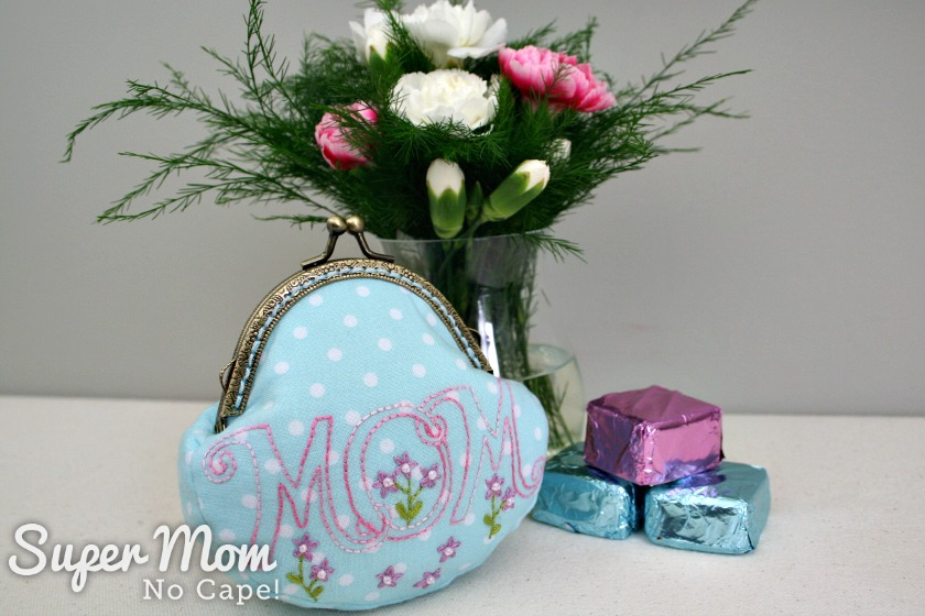 MOM embroidered on the front of the coin purse with vase of flowers and foil wrapped chocolates